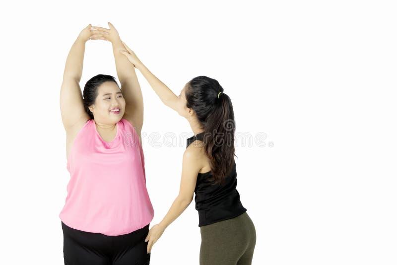 Instructor que ayuda a la mujer gorda que hace estirar imagenes de archivo