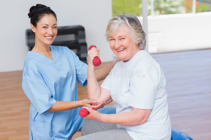 Instructor que ayuda a la mujer mayor en pesas de gimnasia de elevación foto de archivo libre de regalías