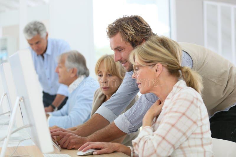 Instructor que ayuda a mayores en clase de la informática imagenes de archivo
