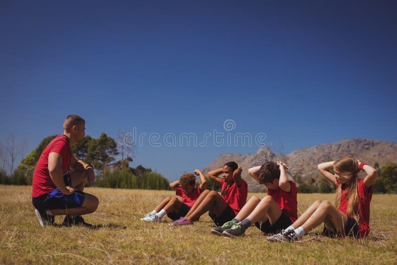 Instructor que da instrucciones a niños mientras que ejercita en el campo de bota fotografía de archivo