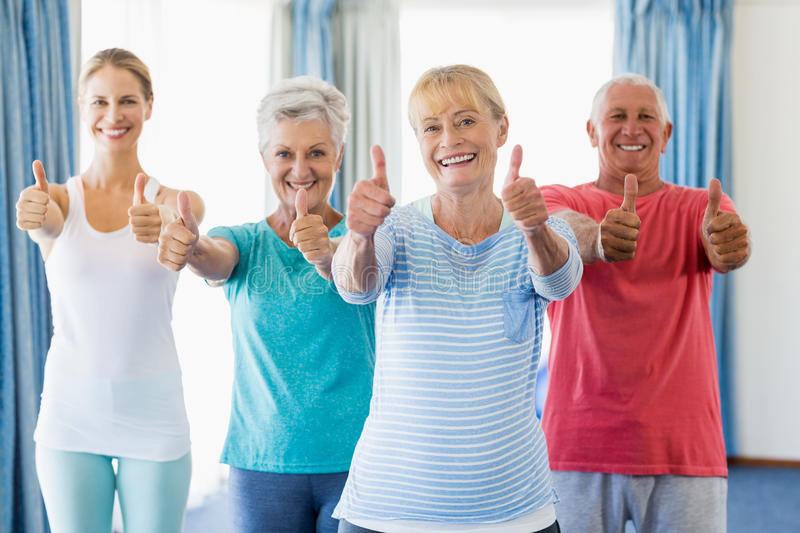 Instructor and seniors with thumbs up royalty free stock image
