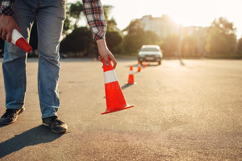 Instructor sets the cone, driving school concept stock photography