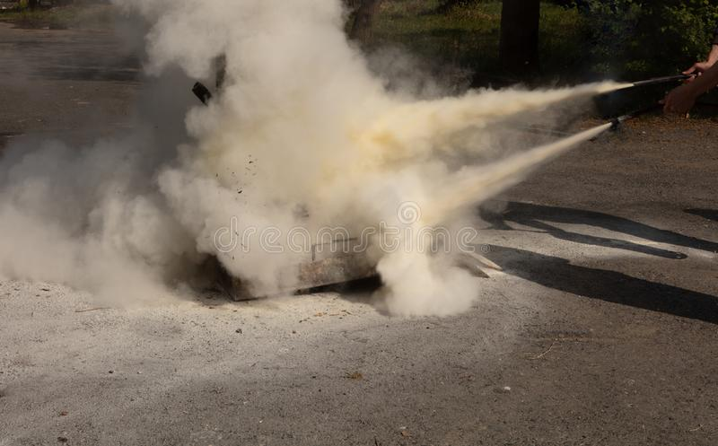 Instructor showing how to use a fire extinguisher on a training royalty free stock photography