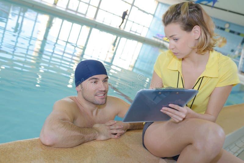 Instructor sonriente que muestra el cronómetro en el nadador en el centro del ocio fotos de archivo