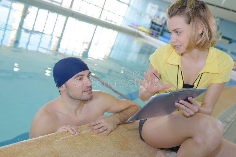 Instructor sonriente que muestra el cronómetro en el nadador en el centro del ocio fotografía de archivo libre de regalías