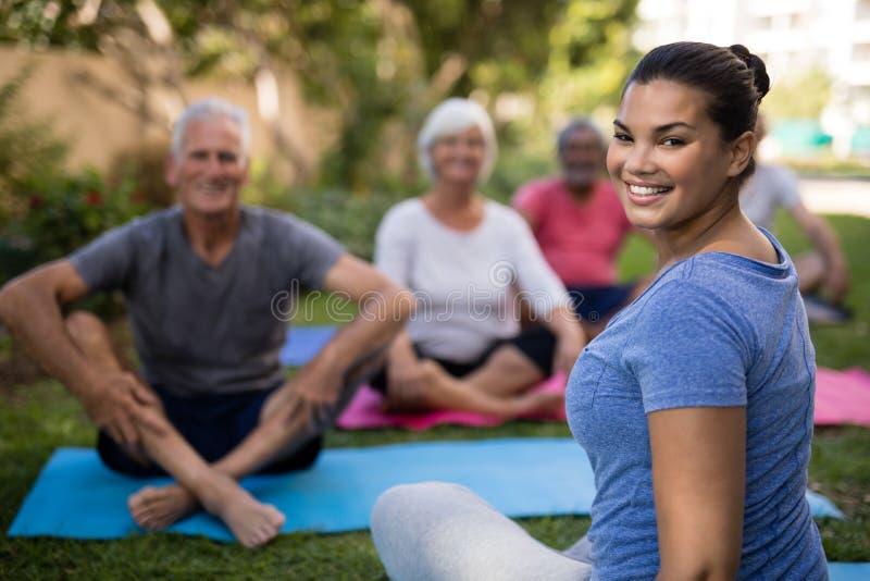 Instructor sonriente que se sienta con la gente mayor mientras que ejercita foto de archivo