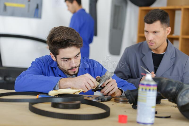Instructor with student in repairshop changing motor oil royalty free stock images