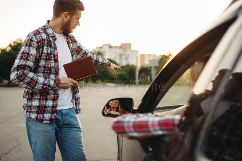 Instructor takes exam, student on driving ground royalty free stock photography
