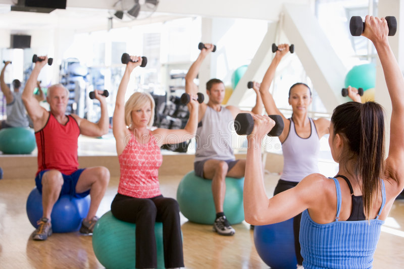 Instructor Taking Exercise Class At Gym royalty free stock image