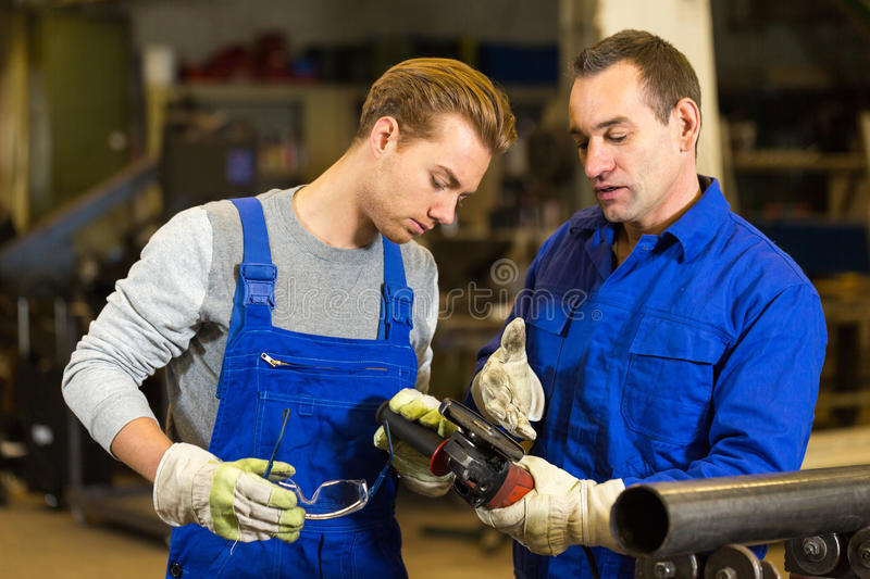Instructor teaches trainee how to use an angle grinder. Instructor teaches steel construction trainee how to use an angle grinder royalty free stock images