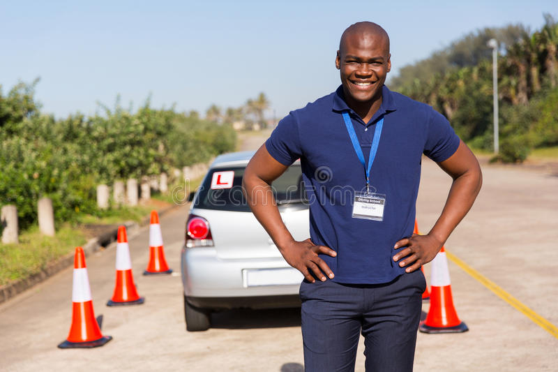 Instructor testing ground. Happy african driving instructor standing in testing ground royalty free stock photos