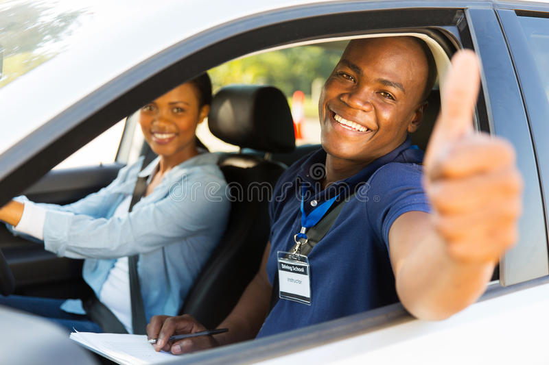 Instructor thumb up. Happy male african driving instructor in a car with learner driver giving thumb up stock image