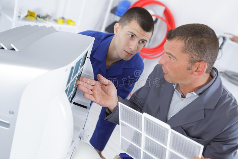 Instructor trains student to repair air conditioning compressor royalty free stock photo