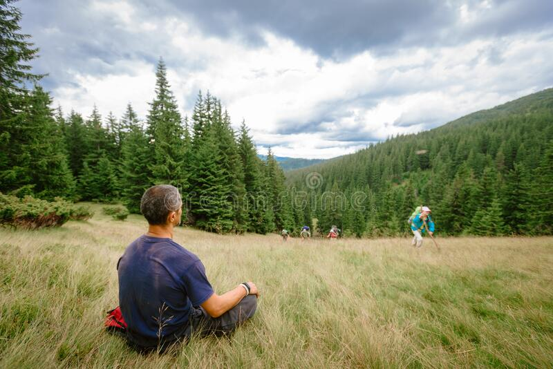 Instructor waiting group. Ivano Frankovsk, Ukraine- July 24, 2019: Male tourist instructor sitting on meadow in Carpathians and waiting the lagging group royalty free stock photography