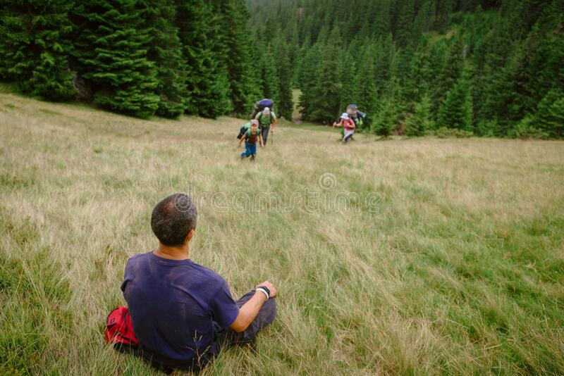 Instructor waiting group. Ivano Frankovsk, Ukraine- July 24, 2019: Male tourist instructor sitting on meadow in Carpathians and waiting the lagging group stock image