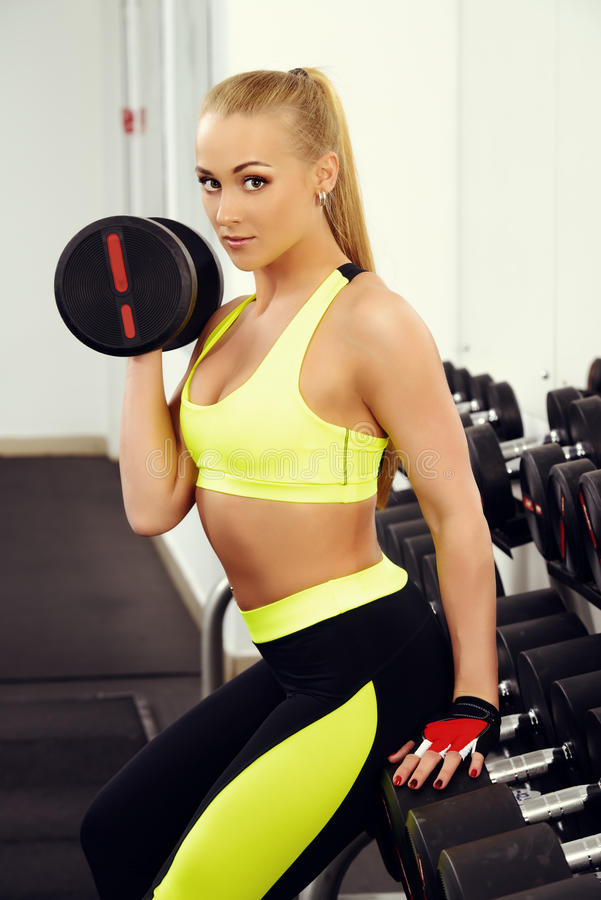 Instructor woman. Slender young woman with beautiful athletic body doing exercises with dumbbells. Fitness, bodybuilding. Healthcare royalty free stock images