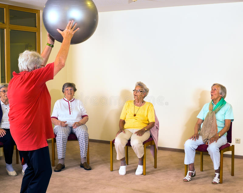 Instructor working with senior ladies in a gym. royalty free stock image