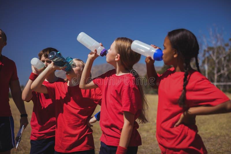 Instructor y agua potable de los niños en el campo de bota imagen de archivo