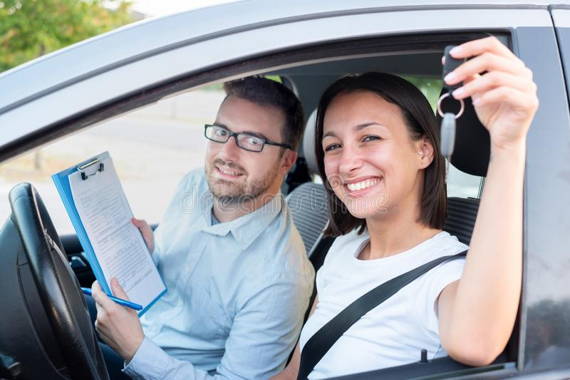 Instructor and young female student, driving lesson. Instructor of driving school giving exam while sitting in car stock image