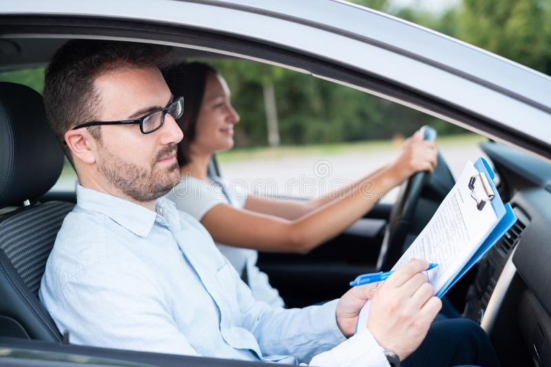 Instructor and young female student, driving lesson. Instructor of driving school giving exam while sitting in car royalty free stock images