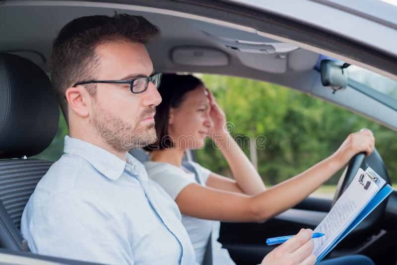 Instructor and young female student, driving lesson. Instructor of driving school giving exam while sitting in car main focus on the instructor stock photography