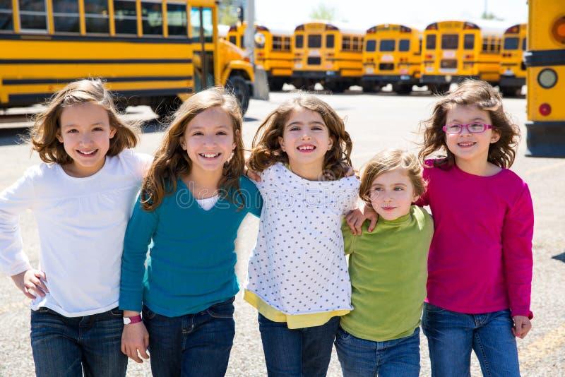 Instruisez amies dans une rangée marchant de l'autobus scolaire images libres de droits