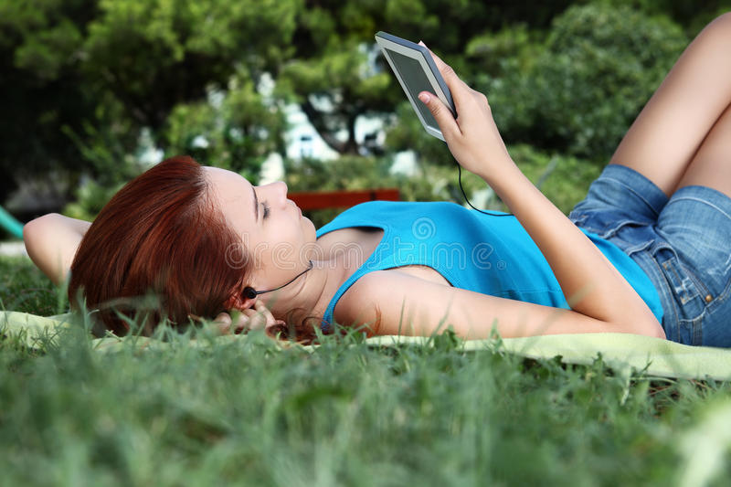 Instruisez la fille au parc avec le téléphone et l'écouteur intelligents image libre de droits