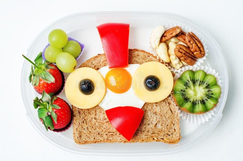 Instruisez la gamelle pour des enfants avec la nourriture sous forme de visages drôles image stock