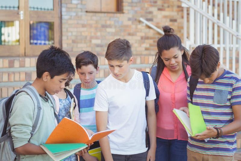 Instruisez les enfants discutant au-dessus du manuel dans le campus images stock