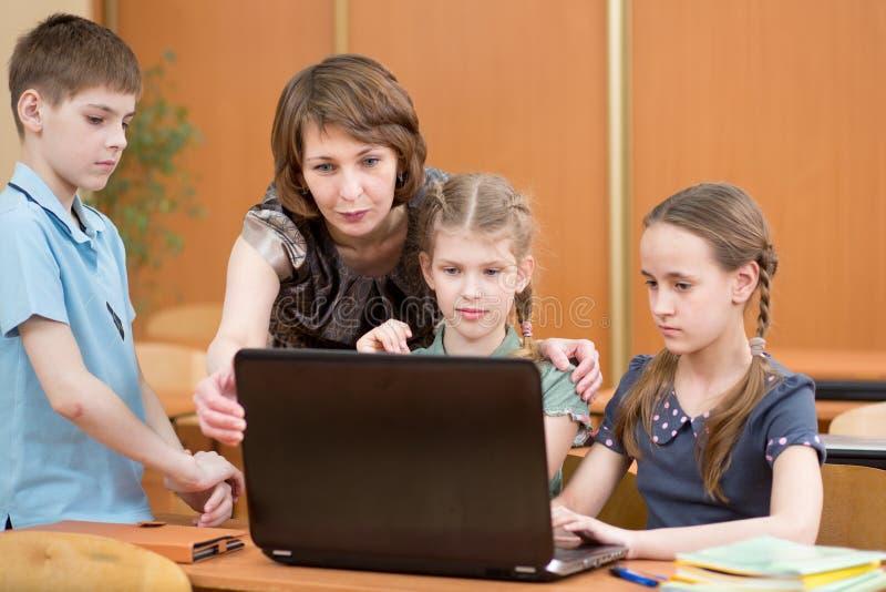 Instruisez les enfants et le professeur à l'ordinateur portable dans la salle de classe images libres de droits