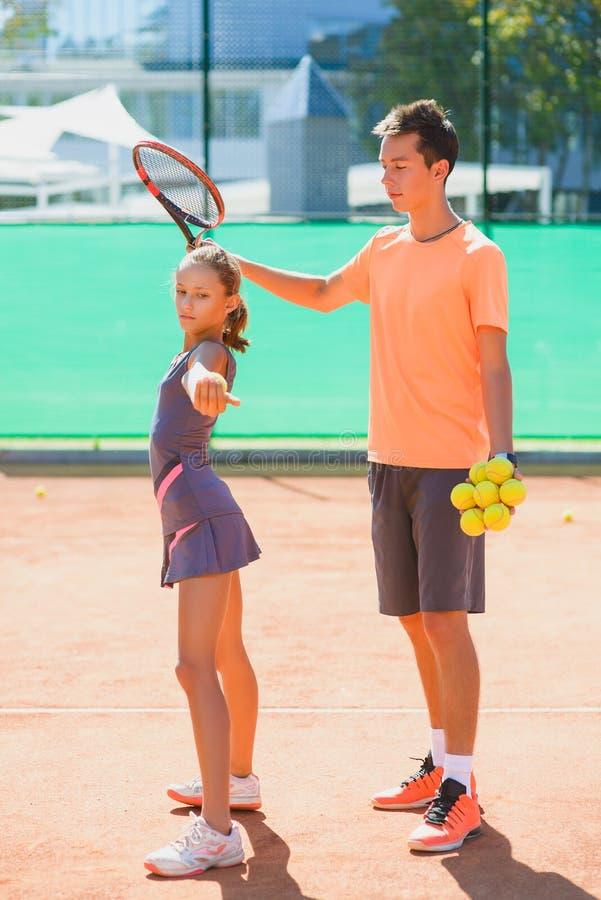 Instruktör- eller lagledareundervisningbarn hur man spelar tennis på en domstol inomhus royaltyfria foton