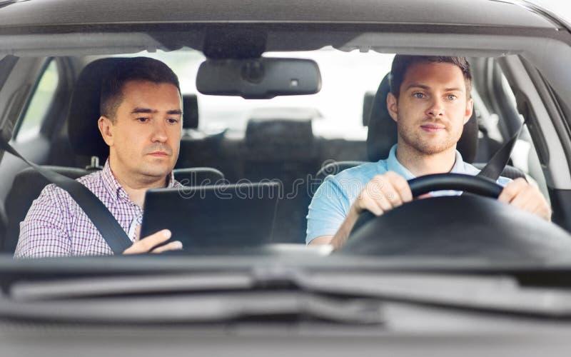 Instruktör i bilkörskola och unga förare arkivfoton