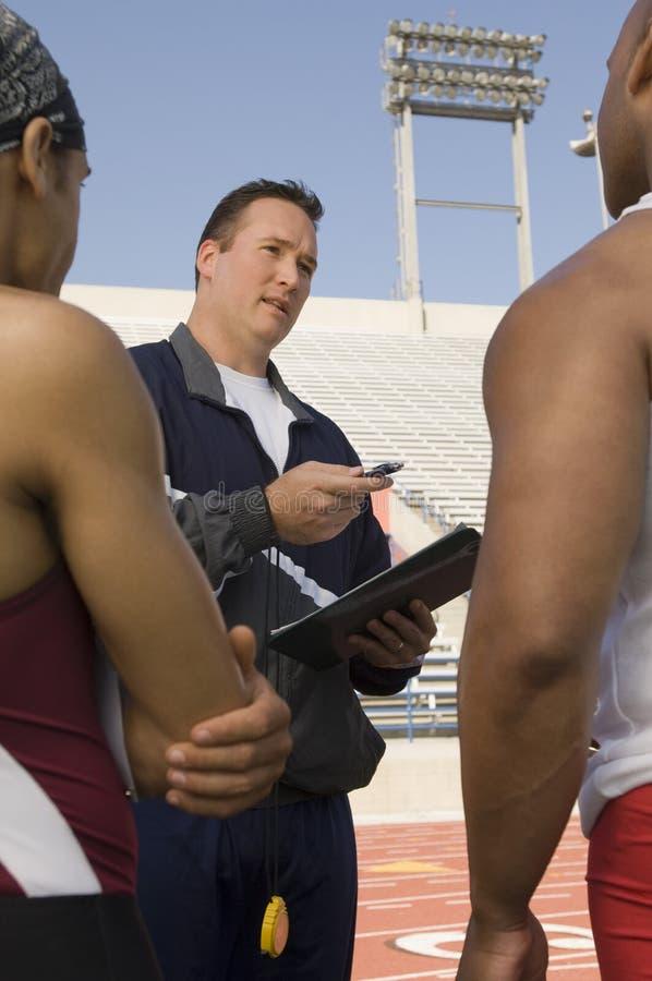 Instruktör Instructing Male Athletes royaltyfri foto