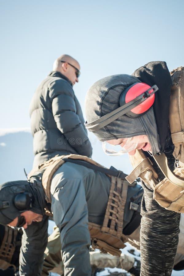 Instruktör- och armésoldater har hård utbildning och göraskjuta-UPS royaltyfria bilder