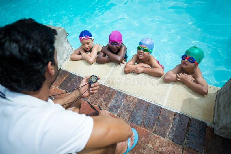 Instruktör som använder stoppuren, medan utbilda små simmare på poolsiden royaltyfri fotografi
