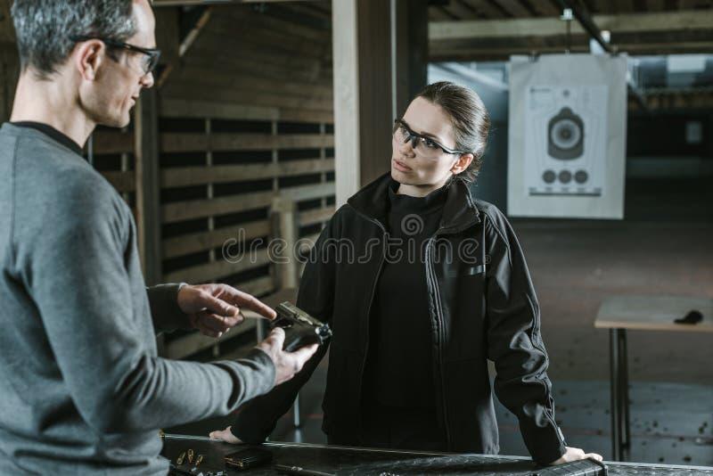 instruktör som beskriver vapnet till den kvinnliga klienten arkivbild
