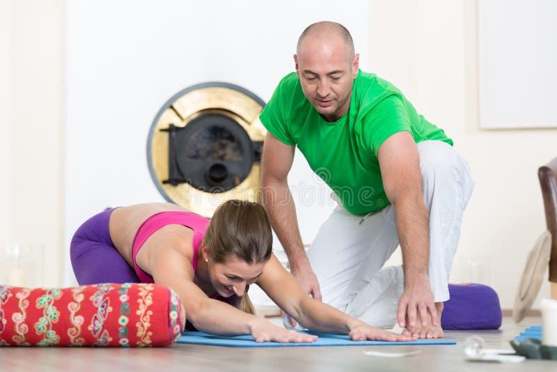 Instruktör som hjälper den kvinnliga studenten att göra yoga för att posera arkivbilder
