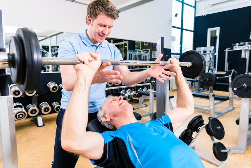 Instruktör som hjälper lyftande skivstången för hög man i idrottshall royaltyfria bilder