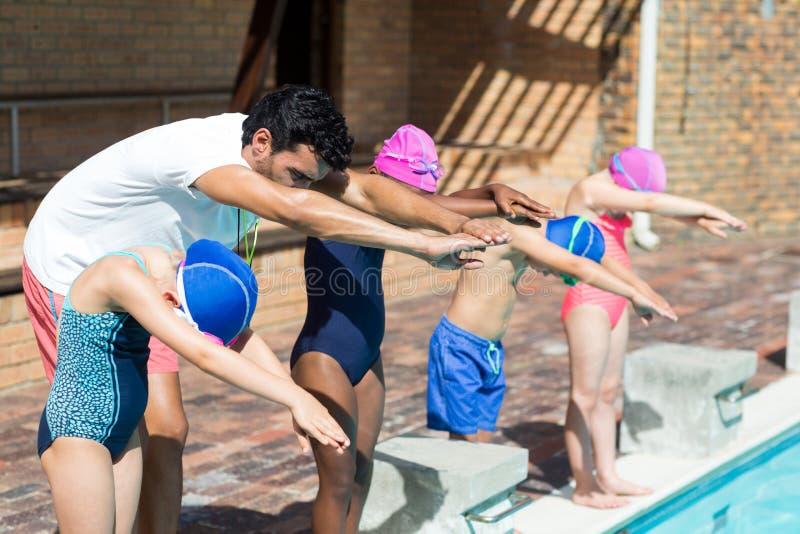 Instruktör som hjälper små simmare för att hoppa i simbassäng arkivfoto