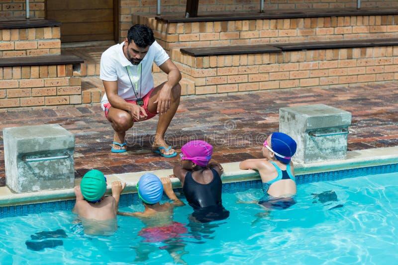 Instruktör som råder små simmare på poolsiden arkivbild