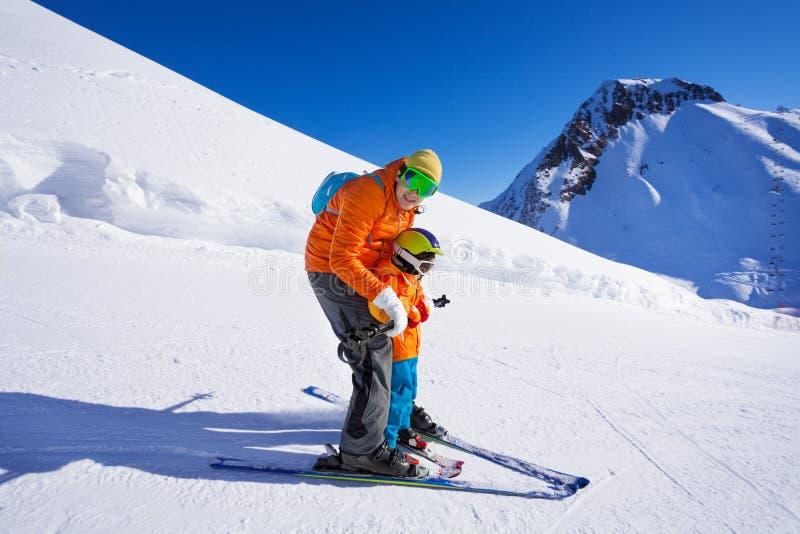 Instruktören ger sig skidar kursen till pysen royaltyfria foton