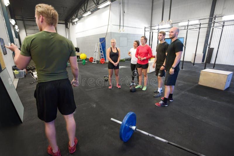 Instruktören undervisar hans konditionlag på idrottshallen royaltyfria foton