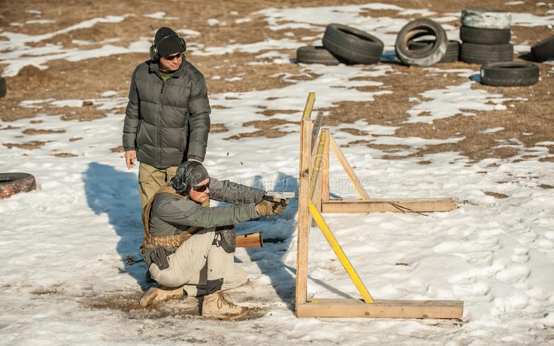 Instruktören undervisar studenten taktisk vapenskytte bak räkningen eller barrikaden royaltyfri fotografi