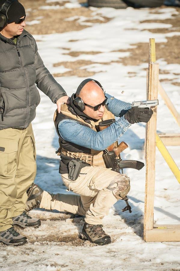 Instruktören undervisar studenten taktisk vapenskytte bak räkningen eller barrikaden arkivfoto