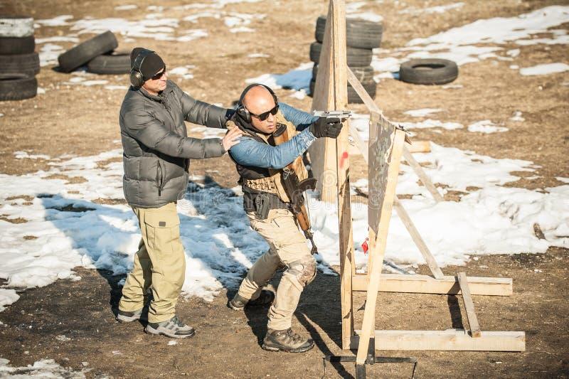 Instruktören undervisar studenten taktisk vapenskytte bak räkningen eller barrikaden arkivfoton