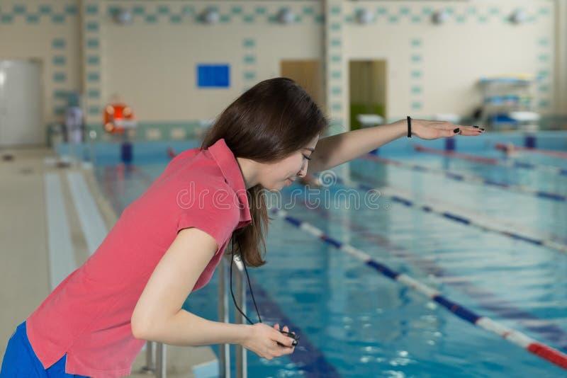 Instruktörkvinna som rymmer en stoppur på poolside och uppförandeutbildning royaltyfri foto