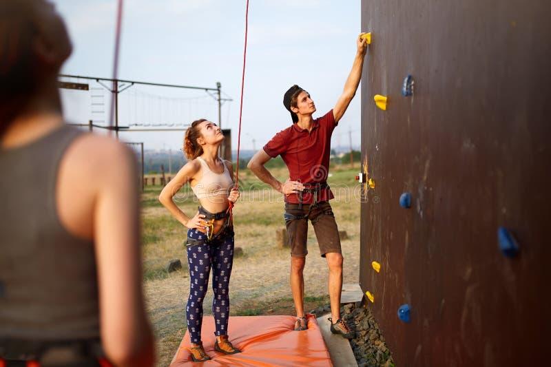 Instruktörmannen som vägleder den nätta slanka caucasian kvinnan vaggar på, klättringutbildningsväggen utomhus Sund livsstil och royaltyfri foto