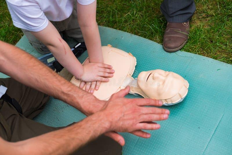 Instruktörshow hur man ger första hjälpen hjärtakompressioner genom att använda attrappen under barnen som utomhus utbildar royaltyfri bild