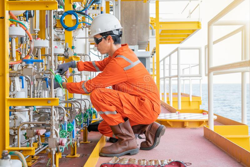 Instrument maintenance technician fixing chemical diaphragm pump at offshore oil and gas wellhead remote platform. stock images