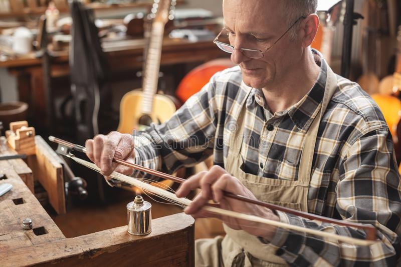 Mature instrument maker inside a rustic workshop is skillfully heating the hair of a violin bow to adjust its length. Blurred back. Ground showing a rustic stock photos